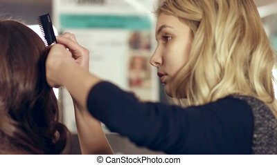 Hairdresser doing up curls of model ,preparing for beauty...