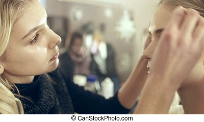 Visagist powders the models face to fix make-up