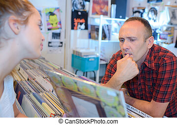 Man and young lady looking at LPs in a record shop