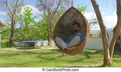 quot;Swinging caucasian man enjoy bird nest hammock swing at...