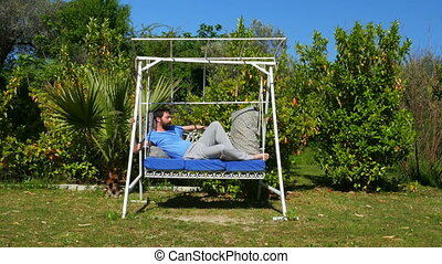 """Swinging caucasian man sleeping on hammock at garden, swing"""