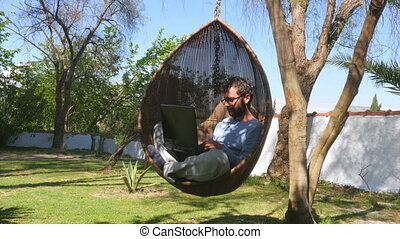 """Freelance worker on hammock swing, working online, typing laptop keyboard"""