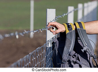 Migrant with backpack on the border - Close up of male hand...