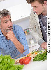 Father and son looking at eachother over vegetables