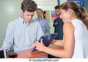 Lady showing clipboard to young man