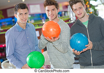 three young men with bowling ball