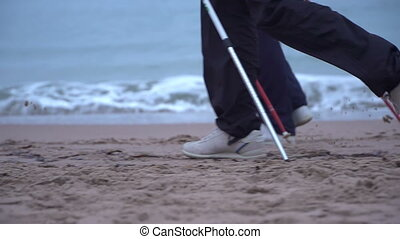 slow motion nordic walking man at Cannes beach