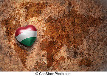 heart with national flag of hungary on a vintage world map...
