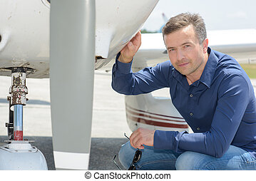 Portrait of man crouching by aircraft