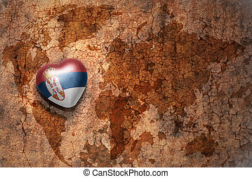 heart with national flag of serbia on a vintage world map...