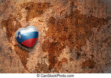 heart with national flag of slovenia on a vintage world map...