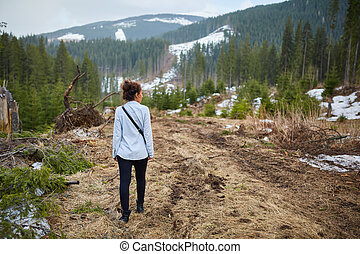 Woman witnessing deforestation aftermath - Woman tourist...