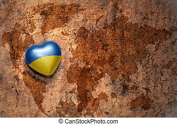 heart with national flag of ukraine on a vintage world map...