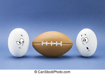 Two eggs look with strange face to a balloon of rugby