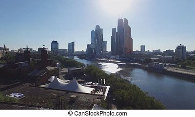 Quadrocopter shoot Moscow International Business Center from riverside. Roof of restaurant. People.