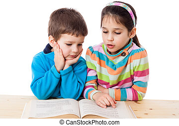 Two kids reading the book at the table