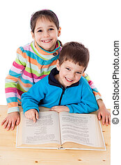 Two happy kids reading the book at the table