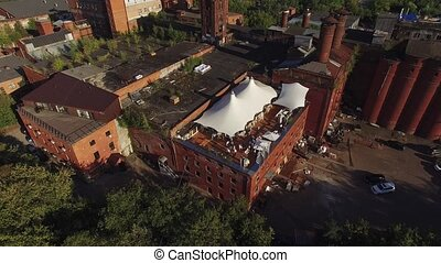 Quadrocopter shoot restaurant with white tents on roof of old brick building. Sunny day. People