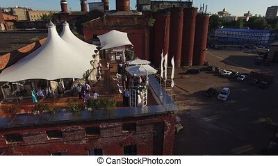 Quadrocopter shoot restaurant with white tents on roof of old brick building. Sunny summer day.
