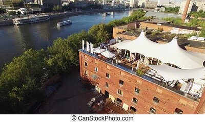 Quadrocopter shoot restaurant with white tents on roof of old building at river. Megapolis. Sunny