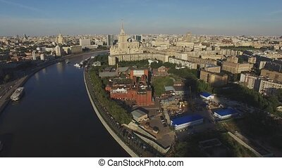 Quadrocopter fly over Moscow city in summer sunny evening. Modern and old edifices. Moscow river.