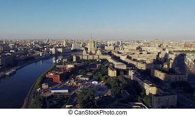 Quadrocopter fly over Moscow city in summer cloudless evening. Modern and old edifices. Moscow river