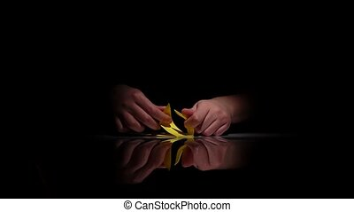 Person makes yellow origami. Black. Closeup - Person makes...