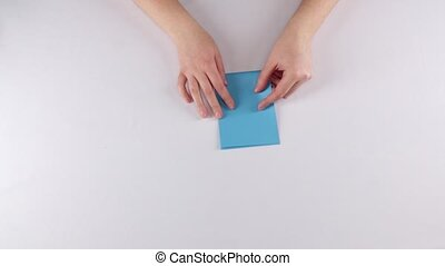 Girl making origami. Envelope. Time lapse - Paper origami...