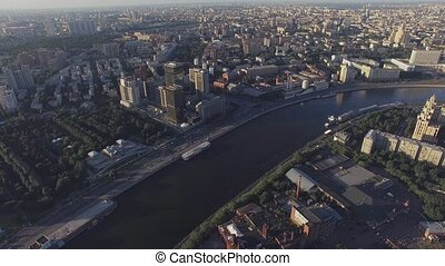 Quadrocopter fly over Moscow river, shoot panorama of city in summer sunny evening. Modern edifices