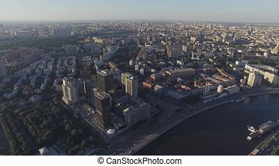 Quadrocopter fly over Moscow river, panoramic view of city in summer sunny evening. Modern edifices