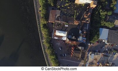 Quadrocopter fly above roof of summer restaurant with white tent. Old building at river. Sunny day
