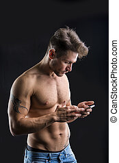 Shirtless muscular young man using cell phone - Handsome...