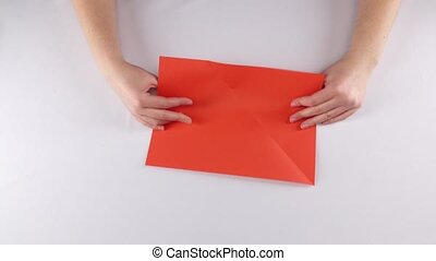 Girl making origami. Red envelope. Time lapse
