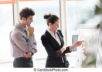 young couple working on flip board at office - successful...