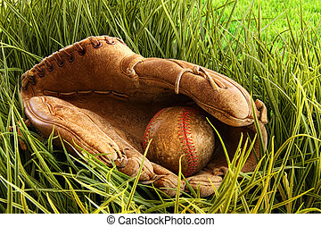 Old baseball glove with ball in the grass - Old leather...