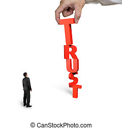 Hand putting T for trust word with small businessman looking...