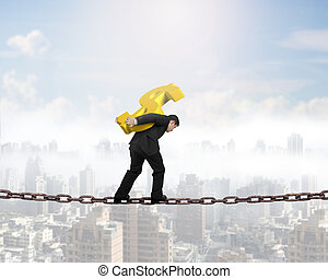 Man carrying golden dollar sign balancing on chain - Man...