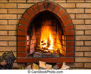 open fire in indoor brick fireplace in country cottage