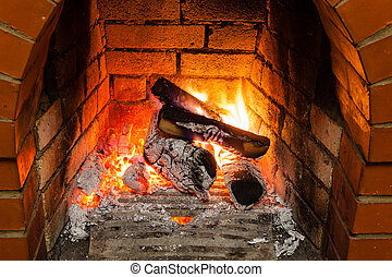 ash, coal and burning wood in fireplace in country cottage
