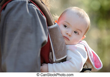 Little baby girl sitting in a baby carrier - Little adorable...