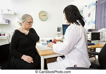 Doctor Explaining Model To Senior Patient Suffering From...