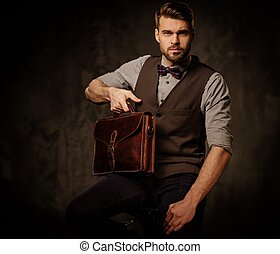 Young handsome old-fashioned man with briefcase posing on...