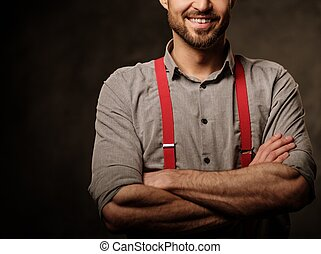 Young handsome man with beard wearing suspenders and posing...