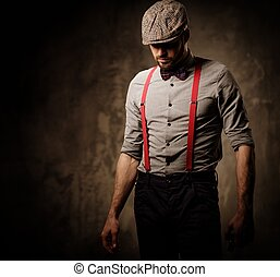 Serious old-fashioned man in tweed hat wearing suspenders...