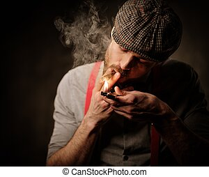 Serious old-fashioned man in tweed hat lighting a cigar on...