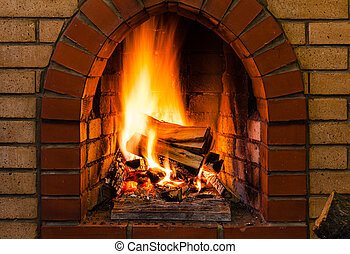 tongues of fire in indoor brick fireplace in country cottage