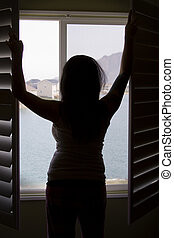 Silhouette of a Woman by the Window Stretching