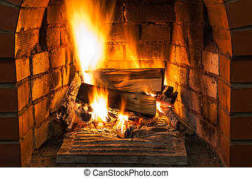 burning wood in brick fireplace in country cottage