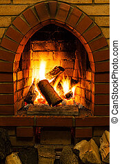 firewood and tongues of fire in fireplace in country cottage