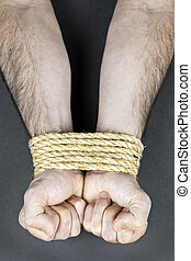 Wrists tied with rope - Male hands tied up with strong rope